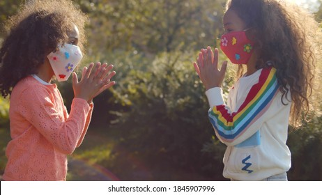 Two afro girls in safety mask playing hand clapping game outdoors. Side view of african sister wearing protective mask having fun together outside on summer day