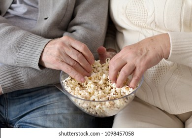 Two aged people eating popcorn together.Hands of elderly people reaching into bowl of popcorn.