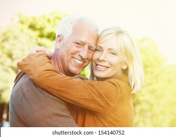 Two aged smiling people over park background