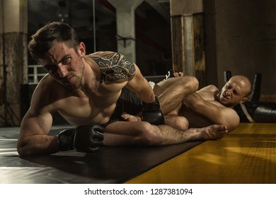 Two aggressive sportsmen wearing gloves and shorts grappling on training in gym. Muscular tattooed MMA fighter with angry expression looking away and keeping with  leg  his opponent lying near.