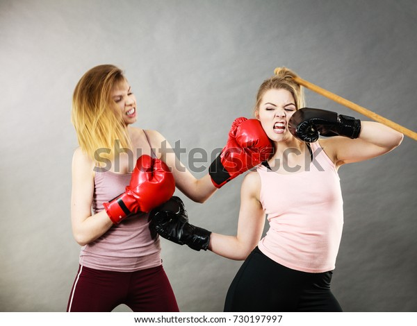 b567df1ca Two agressive women wearing boxing gloves having argue fight being mad at each  other. Female