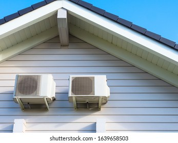 Two air conditioners hang under the roof of the cottage. Sale of air conditioners. Installation and maintenance of climatic equipment. Creation of favorable conditions in the house. Fresh air.