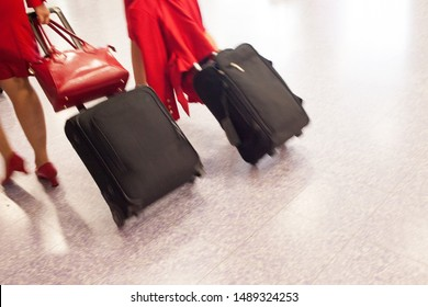 Two air stewardesses rushing with their cabin luggage, to catch their flight. Panning shot, to capture the movement and urgency.