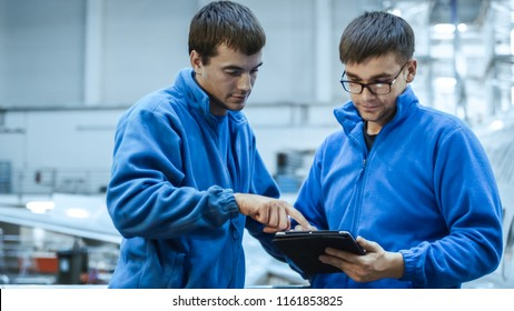 Two aircraft maintenance mechanics have a conversation while using a tablet in a plane hangar.