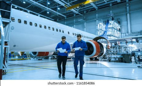 Two aircraft maintenance mechanics have a conversation while checking documents in a plane hangar with an airplane in the background.