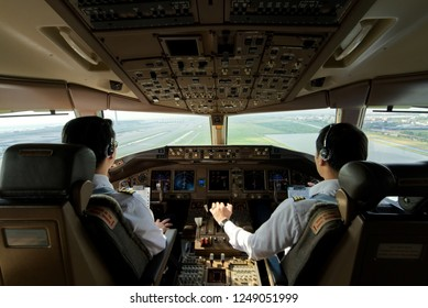 Two airliner pilots are flying the airplane towards the runway. Outside cockpit can see landing runway and airport view. Inside cockpit can see pilots and all flight instrument and equipment.
