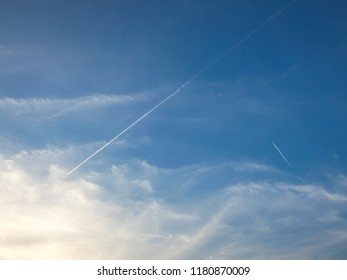 Two airplanes leaving white vapor traces in blue sky with some clouds. Sunny evening. Jet flying.