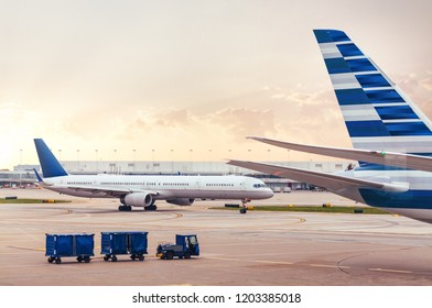 Two airplanes on tarmac with cargo at airport