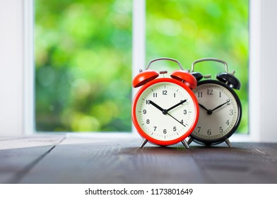 Two alarm clocks with morning sunlight and green bokeh nature background