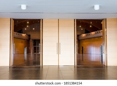 Two aligned open wooden doors on large rich elegant conference hall empty no people front view
