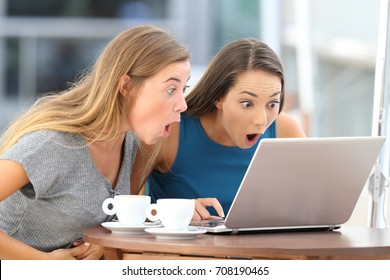 Two amazed friends watching scandalous content in a laptop sitting in a bar