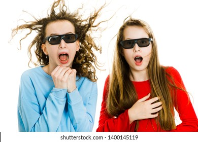 Two amazed teen girls wearing 3D glasses experiencing 5D cinema effect - wind blowing into faces