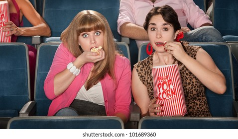 Two amazed women eating popcorn in a theater