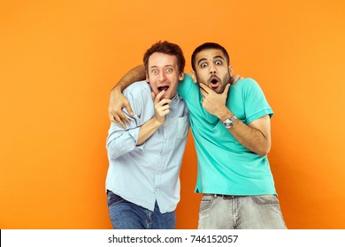 Two Amazement friends hugging, holding his chin and looking at camera with shocked face. Studio shot on orange background