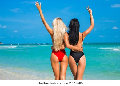 Two amazing tanned girls on the beach, photographed from behind, blonde and brunette, long hair, perfect figures, long legs, fashionable open red and black swimsuits, tropical island, Sexy asses