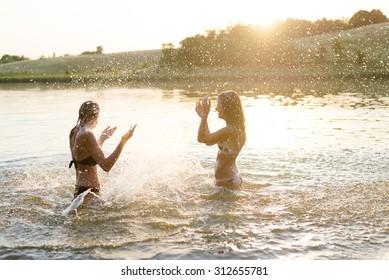 Two amazing young females having fun in lake slushing water