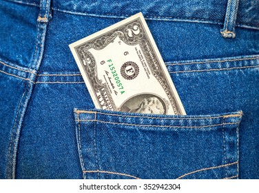 Two american dollars bill sticking out of the back jeans pocket