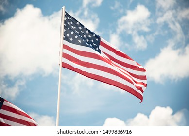 Two American flags fluttering in the wind against a bright blue sky with fluffy white clouds.