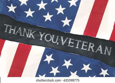 Two American flags made out of paper with text of thank you, veteran on the chalkboard
