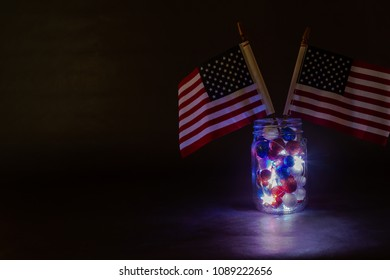Two American Flags in mason jar with lights