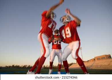 Two American football players, in red football strips, celebrating touchdown on pitch at sunset, jumping chest to chest, teammate looking on, low angle view