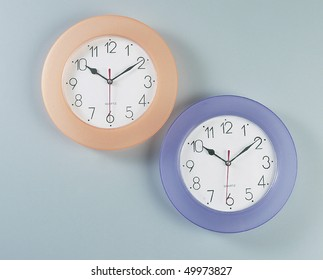 Two analog round wall clock in light blue and orange color