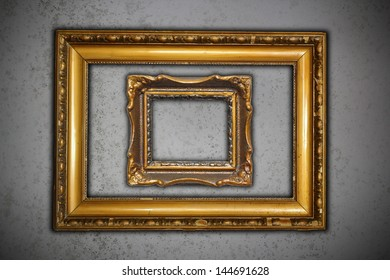 two ancient carved on wood frames for paintings on grungy cement wall