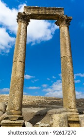 Two ancient Roman columns with capstones support a large flat stone referred to as an abacus. This trio is against a blue sky with a few clouds in Jerash, Jordan.
