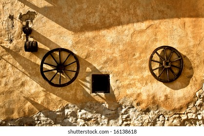 Two ancient wheels on old wall in medieval town