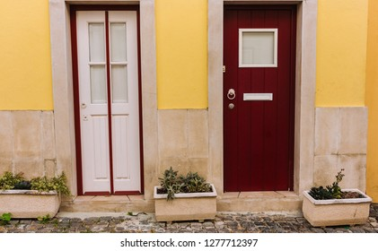 Two ancient wooden doors in Lisbon, Portugal. White and red doors with big flower pots. Traditional portuguese exterior. Entrance concept. Old european architecture. Yellow wall and colorful doors.