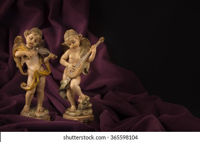 two angel figurines playing musical instruments on purple velvet fabric draped dark background
