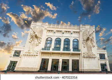 Two angel sculptures with trumpet horns on the front facade of the Bass Performance Hall in Fort Worth, TX taken during the twilight hour