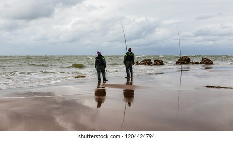 Two anglers fish in the Baltic Sea. Latvia, Kolka. Hobbies, recreation