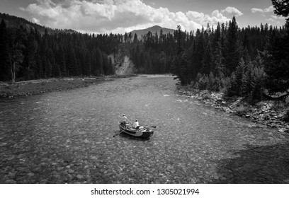 Two anglers float down the South Fork of the Flathead River in the Bob Marshall Wilderness on a warm summer day as viewed from a pack bridge