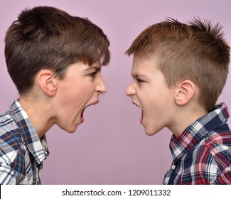 Two angry brothers standing face to face, quarreling, shouting and looking at each other