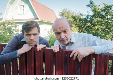 two angry caucasian men carefully watching over the fence. Concept of curious neighbors and private life