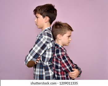 Two angry and frowning brothers standing back to back, not talking to each other