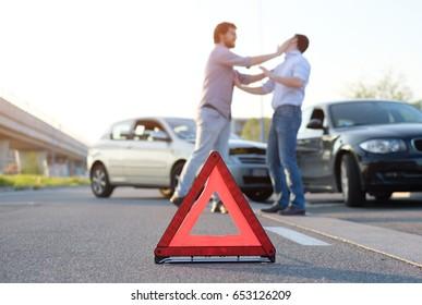 Two angry men arguing after a car fender-bender crash