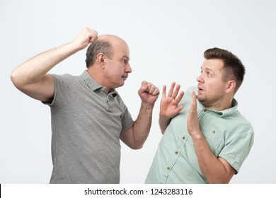 Two angry men facing each others. Family quarrel and disrespect to parents concept