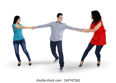 Two angry woman fighting for a man, isolated over white background