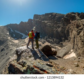 Two anonymous travelers standing on rough rock and admiring picturesque view of majestic mountains in Sierra Nevada, Granada, Spain