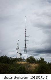 Two antenna pillars on a small hill with grass and bushes. Smaller antenna a bit tilted. Dramatic, cloudy sky. Receiving, broadcast, millitary, secret, radio.