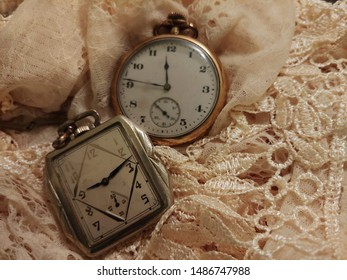 Two antique pocket watches on lace fabric.