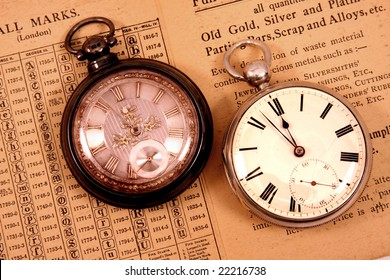 Two antique pocket watches on antique hall mark guide.