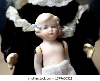 Two antique porcelain dolls, a big and a small one, are together. Big doll holds a smaller china doll on her lap like a big sister holds a small one. Bigger doll wears purple-black dress with lace.