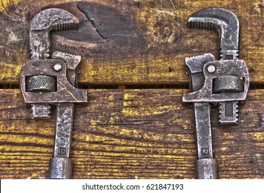 Two antique wrenches on rough wooden background
