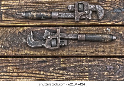 Two antique wrenches on rough wooden background facing each other