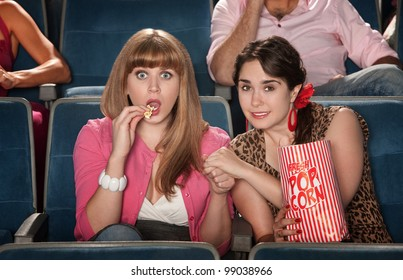 Two anxious women watch movie with bag of popcorn