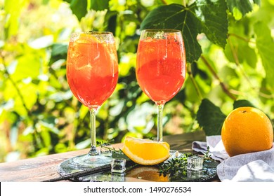 Two Aperol spritz cocktail in big wine glass with oranges, summer Italian fresh alcohol cold drink. Sunny garden with vineyard background, summer mood concept, selective focus