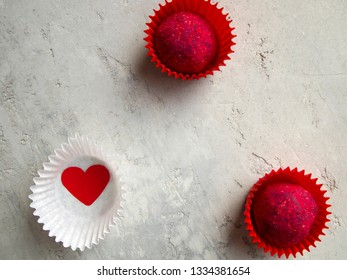 Two appetizing pink candies in red candy wrappers and a red heart in a white wrapper on a gray background. Delicious dark chocolate truffles decorated with sublimated raspberries.